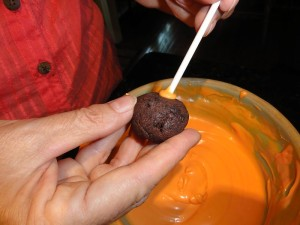 put cake balls onto sticks for cake pops